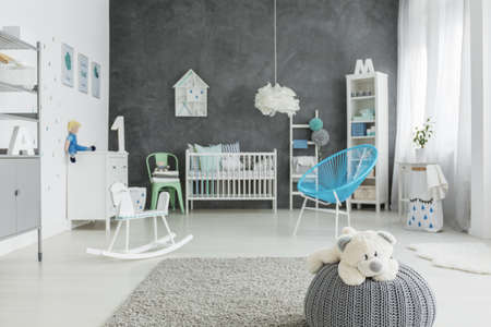 Child room with grey pouf and white cot Stock Photo