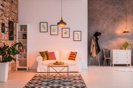 Ruime woonkamer met bakstenen muur, bank, tafel en lamp Stockfoto
