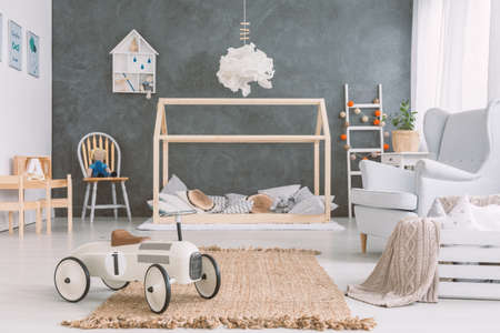 Baby room in scandinavian style with armchair and wood bed Фото со стока