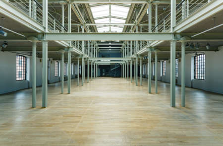 storey: Spacious post industrial factory interior with pillars and windows Stock Photo