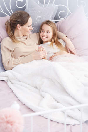 motherly: Young loving mother lying with her daughter under cozy blanket