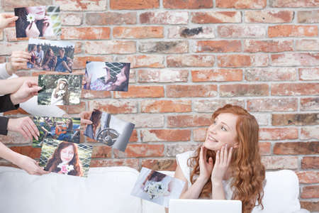 Happy woman watching her pictures, sitting on sofa with laptop