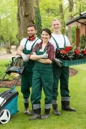 花植物や庭の芝刈りのボックスを持つ幸せな庭師