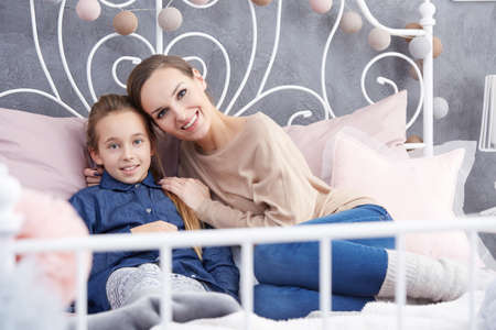 Young pretty woman sitting with her daughter on a bed Stock Photo