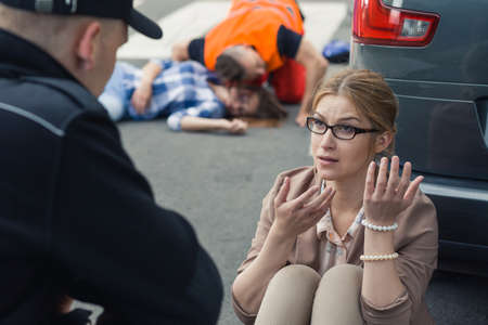 Woman traumatized after car accident talking to policeman while paramedic taking care of victim Stock Photo