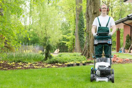 庭師, 緑と芝生芝刈り機が付いている植物の庭に立っています。 写真素材