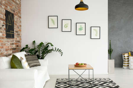 oft: Bright living room with sofa, wall poster and wood table