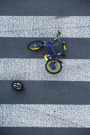 carelessness: Small kids bike lying on the roads zebra crossing after the car accident Stock Photo