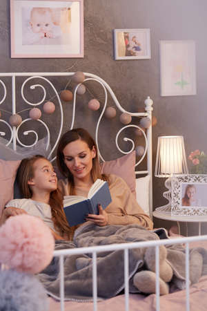 Young mum reading a book to her young daughter