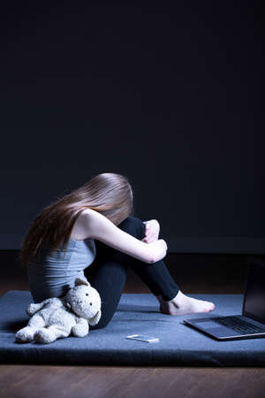 molest: Molested girl with teddy bear and laptop sitting on floor Stock Photo