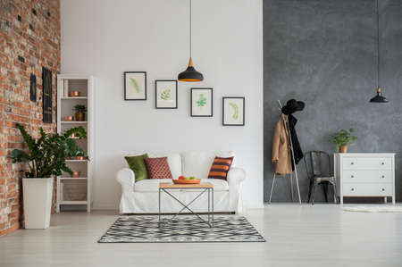 Grijs en wit loft interieur met bank, dressoir en een stoel Stockfoto