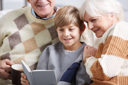 feelings and emotions: Happy, small boy reading book with his grandparents Stock Photo