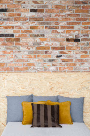 Creative style bedroom with brick wall and OSB bed