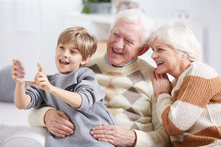 Boy using tablet device, taking selfie with grandparents Stock Photo
