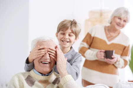 Boy playing with grandfather, covering his eyes Banco de Imagens