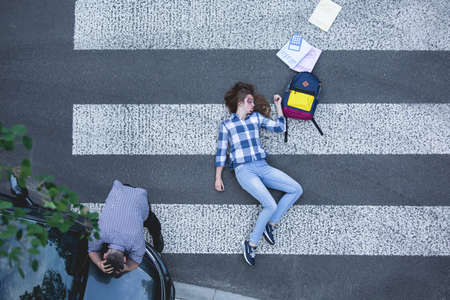 Female student hit by a car, lying on the road next to her school supplies