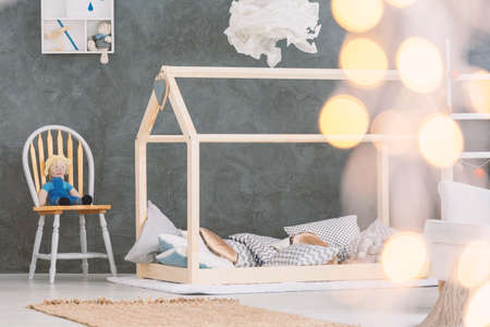 床のベッド、椅子およびコンクリートの壁と赤ちゃんのベッドルーム