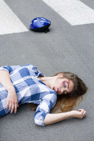 Unconscious and hurt casualty of car accident lying on the road