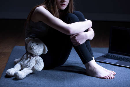 Molested girl with teddy bear sitting on floor Imagens