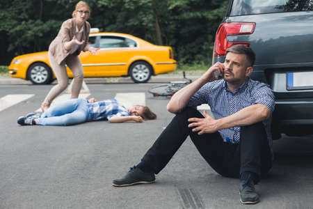 Shot of a shocked man sitting next to his car and calling for help while unconscious victim of the car crash is lying in the background Stock Photo