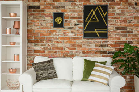 Home interior with brick wall, white couch and copper accessories