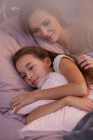 Little daughter sleeping with her young mother in one bed Stock Photo