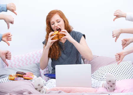 Meisje met laptop, donut eten op bed Stockfoto