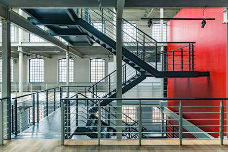 Industrial building interior with red wall and black, metal staircase