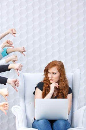 Dissatisfied girl with laptop and people hands with thumbs down