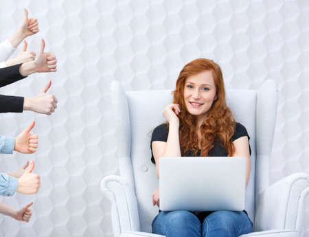 Woman in armchair with laptop, people hands with thumbs up