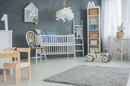 bedroom furniture: Functional baby bedroom with grey wall and white furniture Stock Photo