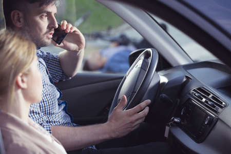 Shocked driver sitting inside his car, calling for a help after car accident