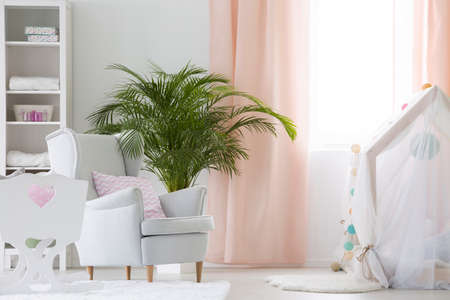 White modern baby room with armchair, crib and plant