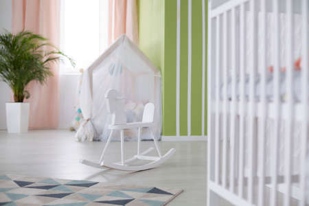 White crib and rocking horse in spacious baby room Stock Photo