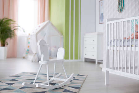 White rocking horse in cozy spacious nursery