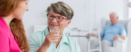 Happy senior woman drinking water from the glass
