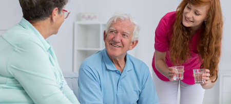 Young and nice nurse taking care of senior man and senior woman Stock Photo