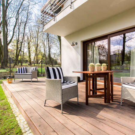Big wooden cozy porch with chairs and coffee table in the back of big residence Stock Photo