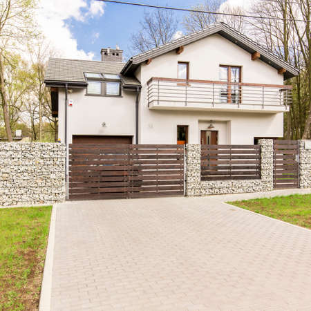 frontyard: Modern white detached house with a driveway and wooden fence