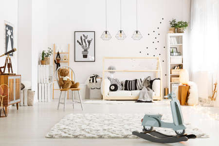 room decor: Spacious child room with bed, chair, lamps and rocking scooter Stock Photo