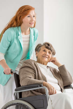 Young nurse helping older disabled woman in nursing home