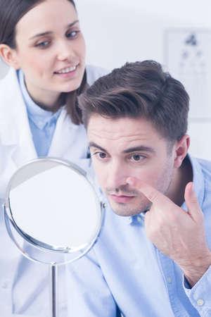 전문 안경점과 콘택트 렌즈를 시도하는 남자