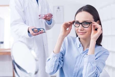 Opticien met oogglazen en cliënt die op nieuwe kaders probeert Stockfoto - 76230475