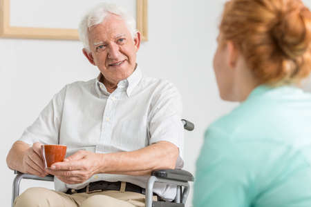 Elderly man on a wheelchair drinking coffee with his carer