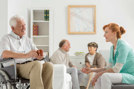 common room: Elderly patients in nursing home talking with young nurse Stock Photo