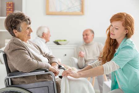 Giovane badante che si prende cura della donna invalida più anziana nella casa di cura Archivio Fotografico - 76230481