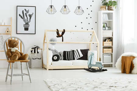 White kid bedroom with house bed, lamps, chair and poster