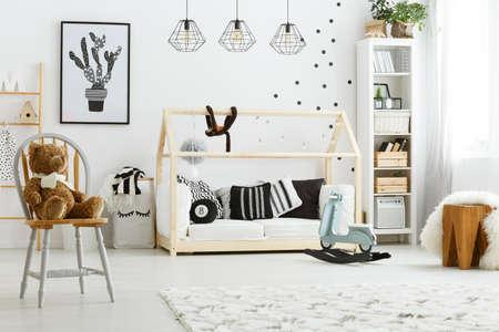 Witte kind slaapkamer met huis bed, lampen, stoel en poster Stockfoto