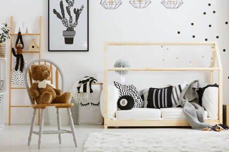 poster bed: Black and white boy bedroom with house bed and chair Stock Photo