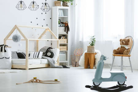 White, child room with toys, bed, lamps, chair and bookcase